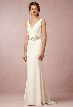 This sophisticated cream crepe gownfeatures an ultra flattering fit : perfectlypin tuckedsurplice neckline, deep cowl back, and a subtle train. Original belt sash included with dress. Straps take in (fabric left so can be used by seamstress) taken in around hips and waist-- American bustle Original bust (V-neck) not altered.