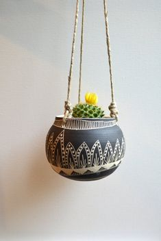 This hanging planter is wheel thrown and hand carved. It measures 4.25 inches high and has a diameter of 2.5 inches. Does not include a drainage hole for