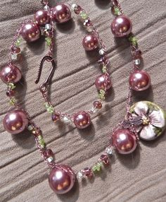 """The spectacular hand made flower accented with a dragonfly is a fun take on a pearl necklace. The pearls are actually a deep coppery pink not the bright of the photo. Set off with crystals and peridot chips on a double layer of crocheted wire, it's 24"""" long.  $48.00"""