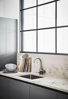 Minimalizm w kuchni nie oznacza nudy. Klasyczne okna z czarną ościeżnicą, kamienny blat, szafki w kolorze szarości i kilka prostych dodatków. Ta kuchni z pewnością jest przykładem minimalistycznego stylu. To jednak wcale nie oznacza, że jest w niej nudno! Zmniejszenie ilości ozdób do niezbędnego minimum spowodowało, że możemy podziwiać piękno materiałów i precyzję wykończenia. A to robi wrażenie! #kuchnia #minimalizm #kamienny #lat ##deska ##do ##krojenia