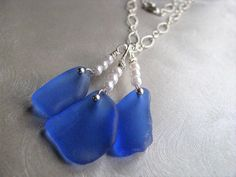 Cornflower Blue Sea Glass Beach Glass Necklace. Cornflower Blue Necklace.... This sea glass necklace pendant has 3 larger pieces of sea glass hanging from 3 tiny pearls above each blue piece and a sterling silver bead pin which dresses up each piece of sea glass. They cluster from a