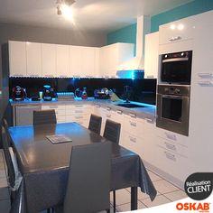 Grande cuisine blanche design et brillante, implantation en L, murs gris et bleu, crédence noire, colonne four micro-ondes, spots lumineux sous meubles hauts- www.oskab.com