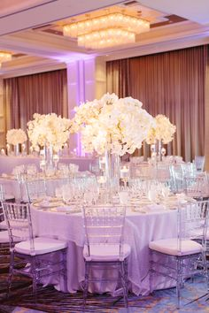 The couple decorated their reception with frosted and clear glass stemware, glass chargers, white linens with a shimmer overlay, clear chiavari chairs and tall arrangements of white phalaenopsis orchids in cylinder vases. Stephanie also made each DIY table number.