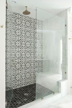 Well appointed walk-in shower boasts a round vintage brass shower head mounted over black hex floor tiles complementing Cement Tile Shop Bouquet III Tiles. Brass Shower Head, Bathroom Shower Tile, Bathroom Makeover, Modern Bathroom, Amazing Bathrooms, Tile Remodel, Cement Tile Shop, Bathrooms Remodel, Bathroom Design