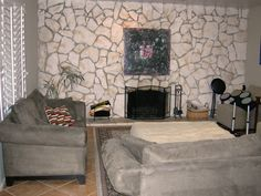 Fireplace Makeovers: Before and Afters From House Crashers: The rock wall in this living room overpowers the small fireplace, and the room's monochromatic color scheme leaves the space feeling dull and dark. From DIYnetwork.com