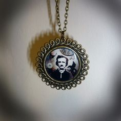 Edgar Allan Poe pendant. Uniquely designed background with vintage watch-parts embedded in resin.    Pendant Size - 4.5cm x 4.5cm    On a 16-18 antique gold tone 16-18 inch chain with an angel wing detail at the end of the extender chain.  £16.99