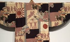 A detail of a boy's kimono from 1933, showing a boy bugler with dog, surrendering Chinese soldiers and the Rising Sun flag.