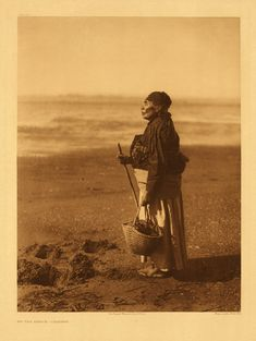 An old Chinook woman with staff and clam basket makes her way slowly over the mud flats of the southern end of Shoalwater bay, in Washington. Chiih (Burden-Basket, Catherine Hawks), is one of a very few survivors of the populous tribe that formerly occupied that part of the state of Washington lying between the middle of Shoalwater bay and the Columbia.