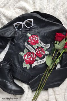 "A faux leather moto jacket featuring a front off-center zipper, a notched collar, side zip pockets, long sleeves with zippered vents, an adjustable belt on the front hem, a back floral embroidery with ""And Now The Adventure Begins"" graphic."