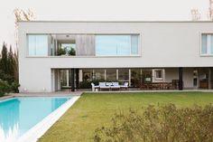 Entre la casa y la galería, patio con granza y abedules. Mesa y sillones de madera con colchonetas de bull blanco. Sobre el piso de cemento alisado, fanales trenzados.  /Magalí Saberian