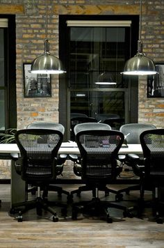 Combine rustic (floor &  bricks) with  modern aeron chairs by Herman Miller