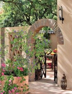 Love the brick arch, wrought iron gates, colorful plantings