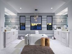 This is a fairy large modern bathroom which has 2 large vanities opposite each other, and a large rectangular bathtub in the middle of the room. The color scheme is white and gray, using white mosaic subway tiles for the floor, white walls, and gray stripe ceramic tiles of the accent wall. To accentuate the tub, a blown glass chandelier hangs right above it.