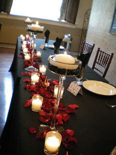I like the red petals as table decorations with the black on black linens.