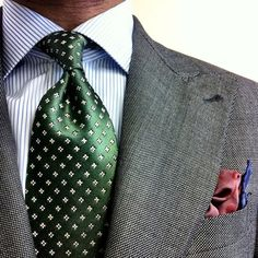 Dark grey jacket with peak lapels, white shirt with blue dress stripes, green tie with white crosses
