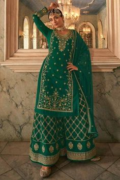 Sway away everyone with your simplicity as you wear this green georgette sharara suit which makes it astonishingly charming. This round neck and full sleeve party wear attire elaborated using stone and zari work. Available with georgette sharara pants in green color with green georgette dupatta. Sharara pants and dupatta perfectly formed using zari and stone work. #shararasuits #malaysia #Indianwear #weddingwear #andaazfashion Indian Attire, Indian Wear, Sharara Suit, Salwar Kameez, Pantalon Cigarette, Pakistani Suits, Costume, Teal Green, Indian Dresses