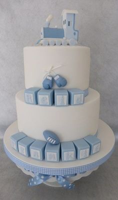 This was a joint christening cake for two cousins, with a special request for the rugby ball and boxing gloves to represent their daddies favorite sports, the train was made from gum paste cut as separate pieces and then stuck together with royal icing