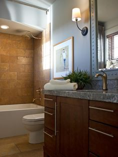 The relaxing spa bath is defined by natural stone tile and warm maple cabinetry, offset by neutral walls.