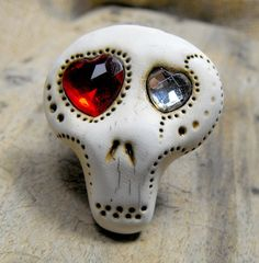 You could make this out of polymer clay. Very simple to construct, Make recesses for the stones for the eyes, and glue then in after 'baking' the clay. Glue your skull onto an old ring, or a new blank. Antique before or after baking to accent details. Skull jewelry for those craving something a little bit different.