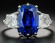 7.18 carats of luscious blue Sapphire perfection, between two delicious epaulette-cut Diamonds and accented with further Diamonds on the sides.