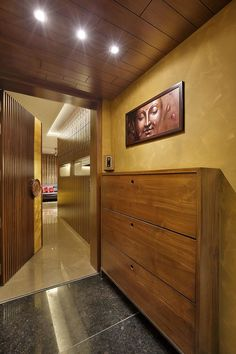 wood art house-the main entrance is designed in teak wood with the customised wooden door handle. the entry wall gives a luxury feel with teak wood