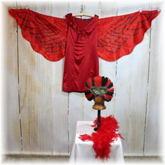 This amazing costume is so versatile youll be able to wear it over and over! You can be a Fiery Red Angel, Phoenix, Red Bird, Red Fairy, or even be a little devilish! This costume is perfect for Halloween, parties, Mardi Gras, or a Masquerade Event! It features a beautiful stretch stain dress, huge 6 foot satin wings that attach with elastic loops on the back of the wings (2 for the arms at shoulder and 1 at each wrist), a feather boa that can be worn around the neck or made into a halo to…