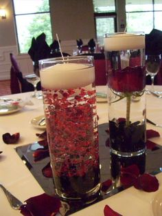 The table centerpieces were a trio of cylinders with submerged roses in two vases and burgundy beaded garlands in one cylinder. White floating candles, black gems and rose petals accented the tables. www.artisticfloraldesign.com