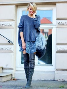 A blue sweater is worn with a floral skirt and suede over-the-knee boots.