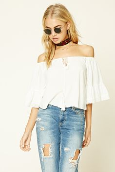 A woven off-the-shoulder peasant top featuring a textured dot pattern, a drawstring neckline with tassels, short bell sleeves with lace trim, and a cropped silhouette.