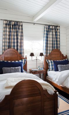 The blue & white color scheme gives a crisp look to this attractive guest room. The stained wood beds keep it from being too light against the white walls. Sightly masculine & nautical but restrained.