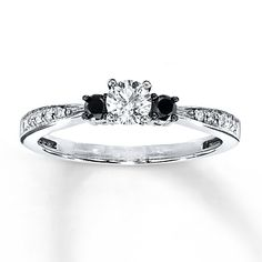 A brilliant round white diamond is graced on either side by a dramatic round black diamond in this remarkable diamond engagement ring for her. Additional white diamonds decorate the 10K white gold band. The ring has a total diamond weight of 3/8 carat. Bl