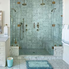 Double door, double head shower with benches in beautiful Carrara marble.
