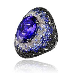 Ring in white gold with tanzanite center, surrounded by colorless diamonds, black diamonds and blue sapphires by Aspire, Hong Kong.