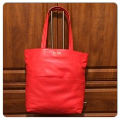 """COLE HAAN FIERY RED TOTE 100% genuine leather. The color is called Fiery Red but it has a little orange to it. Measurements are 14"""" long, 16"""" wide. Handle drop is 21-1/2"""". Brand new with tags. Comes with a dustbag. Please make a reasonable offer Cole Haan Bags Totes"""