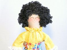 Meet Eileen!  Eileen is a handmade rag doll, standing 10.5 inches (26.75 cm) tall.  She has am ecru body made from egyptian cotton, stuffed with polyester fiberfill.  She has curly black rayon hair.  Her green eyes and pink smile are hand embroidered. Eileen is wearing a bright yellow blouse with white lace trim at the cuffs.  Her A-line skirt closes in the back with Velcro®.  Eileen is also wearing white pantaloons with white lace trim.  All of her clothes are machine wash and dry on ...