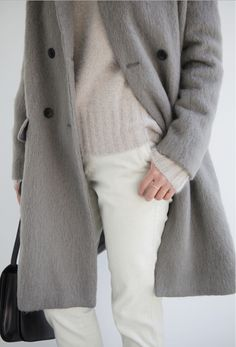 Light grey coat with cream sweater and cream cords. Love the three thin rings, one on each finger.