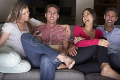 Group Of Friends Sitting On Sofa Watching TV Together