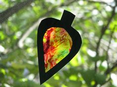 """""""Stained glass"""" melted crayon project: old crayons, wax paper, iron, construction paper, glue, scissors, and scrap cloth or paper towels."""