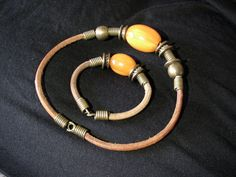 made of leather strap with metal and coral stones,a very nice set of bracelet and necklace yemenite style desigen,from the year 1974. i found it last night in the family's attic and i fell in love with the authenticity and the charm this set shows.