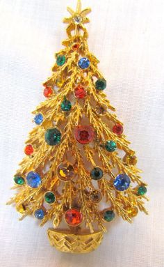 This is a beautiful ART Christmas tree pin in a gold tone metal with a variety of colored rhinestones and a star on the top to make it look super