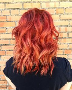Bright vibrant red Aveda hair color on a tousled wavy lob by Evolve Hair Studio.