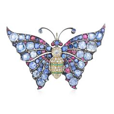 Designed as a butterfly brooch, crafted out of 18K yellow gold and sterling silver, with wingsfeaturing a colorful assortment of bead-set sapphires, weighing a total of approximately 48.00 carats, further enhanced by bead-set rubies, weighing a total of approximately 3.60 carats, decorated with 58 round-cut diamonds, weighing a total of approximately 0.40 carats, with the body section being crafted out of 18K yellow gold, featuring a rose-cut diamond, weighing approximately 0.55 carats…