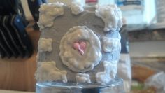 This is companion cube 1.2.  The cake itself is a rum cake I made.  I used my mini cake tins, sliced each cake in half and used 3 slices to get the cube shape.  I used a white chocolate icing I invented and went from there.  I'm going to work on the icing for next time as well as the cake batter.  The cake was a bit too soft and the icing didn't harden as much as I was hoping.  You guys will be the first to see 2.0!