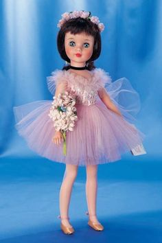 """Polly"" Ballerina by Alexander 17"" (43 cm.) Vinyl socket head,sleep eyes,brunette rooted hair with bangs and tied-back long curls,five piece body,wearing pink tulle tutu with richly sequined bodice,black velvet neck ribbon,pink stockings,gold ballerina slippers,large floral spray in arms,and floral coronet. Marks: Alexander 1965 (doll) ""Polly"" Alexander (costume). Very fine original unplayed with condition,crisp and fresh costume and accessories,rosy cheeks,original Polly wrist booklet,original box labeled ""Polly 1725"". Alexander,1965. Z"