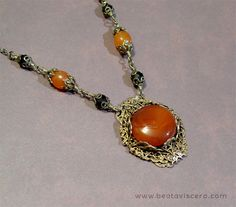 Handmade antique brass necklace with brass filigree wrap, carnelian and black Czech crystal beads.