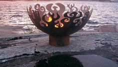"""Made from recycled steel, The Great Bowl O' Fire is a sculptural piece,  the hand cut fire pit spheres by artist Melissa Crisp. The 37""""-diameter bowl seems in flame even when the actual flame is not on! Stunning at floor level, it gains an """"Olympic"""" feel when raised on a pedestal."""