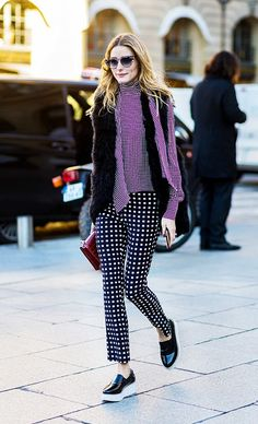 Olivia Palermo wears a check high-neck top, fur vest, printed trousers, and platform sneakers