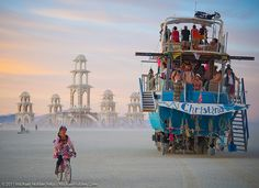 A cyclist and an enormous art fishing boat cross paths at Burning Man 2011 / Washoe County, Nevada, USA
