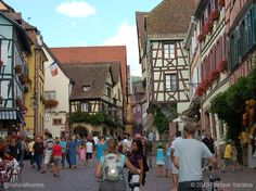 This is one of the bustling streets of Riquewihr in the Alsace region of France. It's typical of many of France's small medieval towns where the ancient protected buildings are too small and wonky for supermarket chains and franchises to dismantle and shoehorn in their model businesses. More at www.naturalhomes.org/pattern87