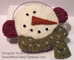Wooly snowman ornament.  Hand sewn with a blanket stitch and slightly stuffed.